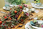 Autumn table decoration: horn of plenty with Ilex, chrysanthemums