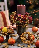 Eine brennende Kerze auf einem herbstlich dekorierten Tisch