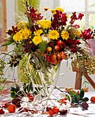 Vase of ornamental apples, chrysanthemums & snapdragons