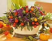 Arrangement of blue potato bush flowers and ornamental peppers