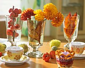 Ornamental apples, chrysanthemums & foliage in wine glasses