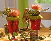 Wine glasses with moss wreaths, Protea flowers & Hypericum