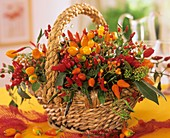 Arrangement of ornamental peppers and rose hips in basket