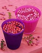 Pernettya berries floating in pink and purple glasses