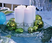 White candles and Christmas baubles on glass plate