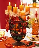 Adventskranz mit Baumschmuck, Orangen und Äpfeln