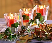 Wine glasses with sand and red candles, autumn leaves