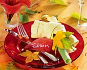 Plate decoration: autumn leaves and yellow napkin