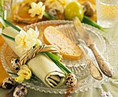 Place setting with narcissi, quail's eggs and slice of bread