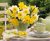 Vase of daffodils on table laid for coffee
