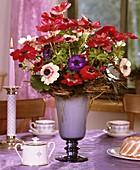 Tisch mit Kronenanemonen, Tassen und Mini-Gugelhupf