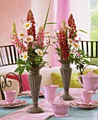 Pink crockery & arrangement of lupins, marguerites, ragged robin