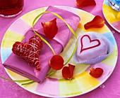 Sisal heart on purple napkin, petit four and rose petals