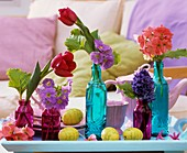 Coloured glass bottles with spring flowers and Easter eggs