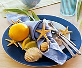 Place-setting decorated with orange, starfish and sea shells