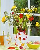 Strauss aus Freesien und Wachsblumen, Schale mit Süssigkeiten, Filzblüten
