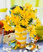 Vase of yellow marguerites, fish and shells
