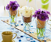 Pansies and Ranunculus in glasses with birch bark