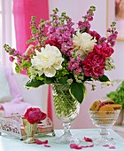 Arrangement of peonies and stocks, bowl of biscuits