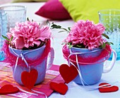 Carnations in blue cups decorated with sisal and hearts
