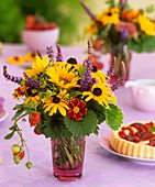 Rudbeckias, sunflowers, strawberries and dill in a glass