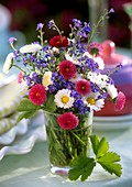 Forget-me-nots and daisies in a glass