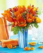 Orange tulips and dead-nettle in blue striped vase
