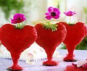 Rote Sisalherzen mit Anemonen in Reihe arrangiert