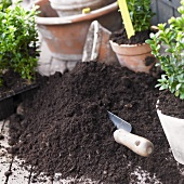 Garden soil with trowel, flowerpots