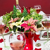 Christmas table with floral decoration and glasses of rosé wine