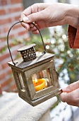 Hand holding lantern with candle