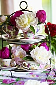 Arrangement of peonies in cups and saucers on tiered stand