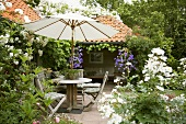 Sitting area with sunshade in summery garden