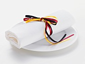White fabric napkin tied with ribbon in colours of German flag