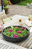 Seerosenblüten und Schwimmpflanzen in Wasserschale auf Gartentisch