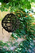 Woven willow ball hanging on pergola