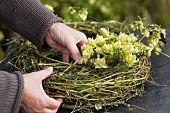 Inserting hop tendrils into wreath of twigs