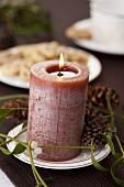 Kerze mit Mistelzweig und Pinienzapfen