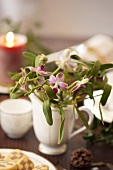 Orchids and mistletoe in small jug