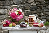 Chocolate cake with cream and jam filling, flowers, bottled pears and jam