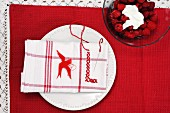 Raspberries with whipped cream beside plate with napkin