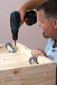 Mann schraubt Rollen in eine Holzkiste