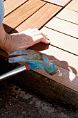 Woman hammering screw into wooden edging