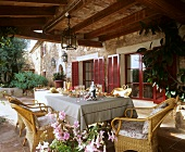 A table laid with appetizers and sparkling wine on a covered patio of an old, French country house