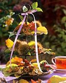 Etagere mit Esskastanien, Bucheckern und Herbstlaub