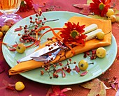 Place-setting decorated with rose hips and chrysanthemum
