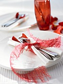 Place-setting with red napkin decoration