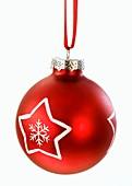 Eine rote Christbaumkugel mit weißem Stern