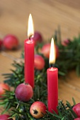 Christmas yew wreath with ornamental apples & two red candles