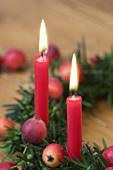 Weihnachtskranz aus Eibe mit Zieräpfeln und zwei roten Kerzen